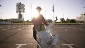 Rozochocona pary jazda z wózkiem na zakupy blisko supermarketa, szczęśliwy kobiety obsiadanie w tramwaju i ono uśmiecha się, zdjęcie wideo