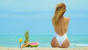 Rozochocona piękna młoda dziewczyna siedzi z ich plecy na plaży morzem zdjęcie wideo