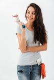 Rozochocona piękna młodej kobiety pozycja i mienie farby rolownik Obrazy Royalty Free