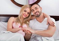Rozochocona piękna para pozuje w rodzinnym łóżku Obraz Stock