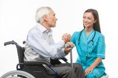 Rozochocona potomstwo pielęgniarka trzyma starszego mężczyzna rękę i sm obraz stock