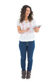 Rozochocona przypadkowa brunetka używać jej pastylka komputer osobistego Fotografia Stock