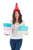 Rozochocona przypadkowa brunetka z partyjnymi kapeluszowymi mienie teraźniejszość Obrazy Royalty Free
