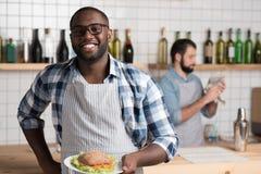 Rozochocona przystojna kelner pozycja z smakowitymi ono uśmiecha się i kanapką fotografia stock