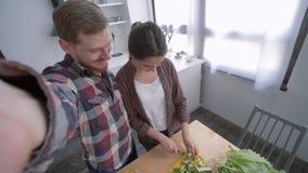 Rozochocona rodzina w kuchni, młoda kobieta z mężczyzny wp8lywy selfie fotografią na telefonie komórkowym podczas gdy gotujący zd zdjęcie wideo