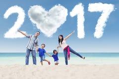 Rozochocona rodzina z chmurą 2017 przy plażą Obrazy Stock