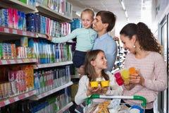 Rozochocona rodzina z dwa córkami nabywa jogurty zdjęcia royalty free