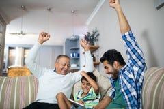 Rozochocona rodzina z rękami podnosił być usytuowanym na kanapie fotografia stock