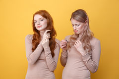 Rozochocona rudzielec dama dotyka jej włosianej pobliskiej smutnej blondynki kobiety fotografia royalty free