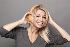 Rozochocona 20s dziewczyna cieszy się muzykę na hełmofonach obrazy royalty free