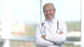 Rozochocona senior lekarka, zamazany tło zbiory