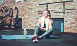 Rozochocona sporty kobieta siedzi i pisze puszkowi przyszłościowych stażowych planach dla dokonywać wielkich rezultaty w gym i od obrazy stock