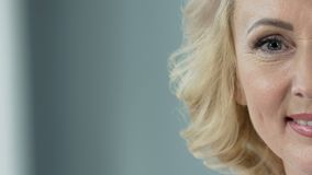 Rozochocona starsza blondynka ono uśmiecha się w kamerę, chirurgii plastycznej klinika, zakończenie zbiory