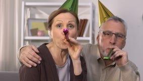 Rozochocona starsza para świętuje urodziny w partyjnych kapeluszach, robi niespodziance zbiory