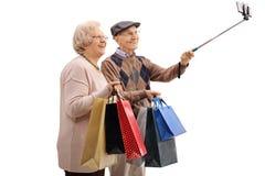 Rozochocona starsza para z torba na zakupy bierze selfie Obrazy Royalty Free