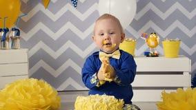 Rozochocona, szczęśliwa jeden rok chłopiec pożera tort z jego, ręki zbiory