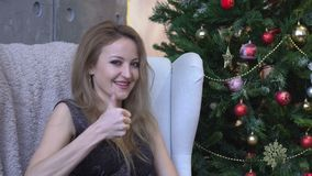 Rozochocona szczęśliwa młoda kobieta pokazuje kciuk up na choinki tle zbiory