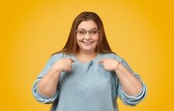 Rozochocona tłuściuchna kobieta wskazuje przy ona obrazy royalty free