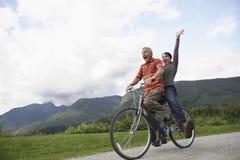 Rozochocona W średnim wieku para Bicycling Na wiejskiej drodze Zdjęcia Stock