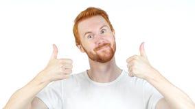 Rozochocone czerwone włosiane mężczyzna aprobaty pozuje i ono uśmiecha się przy kamerą, biały tło fotografia royalty free