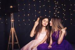 rozochocone dziewczyny Dwa dziewczyny czeszą each innego ` s włosy, siedzi stronę popierają kogoś w studiu na ciemnym tle - obok  Zdjęcia Royalty Free