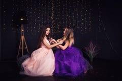 rozochocone dziewczyny Dwa dziewczyny czeszą each innego ` s włosy, siedzi stronę popierają kogoś w studiu na ciemnym tle - obok  Zdjęcia Stock