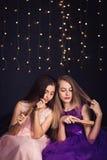 rozochocone dziewczyny Dwa dziewczyny czeszą each innego ` s włosy, siedzi stronę popierają kogoś w studiu na ciemnym tle - obok  Zdjęcie Royalty Free