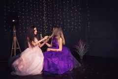 rozochocone dziewczyny Dwa dziewczyny czeszą each innego ` s włosy, siedzi stronę popierają kogoś w studiu na ciemnym tle - obok  Fotografia Royalty Free