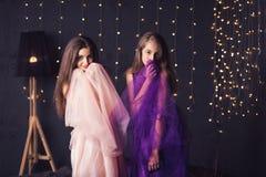 rozochocone dziewczyny Dwa długowłosej dziewczyny w menchii i purpur sukniach w studiu na ciemnym tle z bokeh kosmos kopii Fotografia Royalty Free