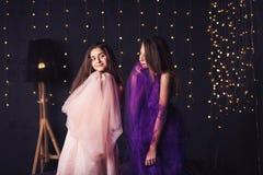 rozochocone dziewczyny Dwa długowłosej dziewczyny w menchii i purpur sukniach w studiu na ciemnym tle z bokeh kosmos kopii Zdjęcie Stock
