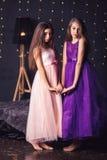 rozochocone dziewczyny Dwa długowłosej dziewczyny w menchii i purpur sukniach w studiu na ciemnym tle z bokeh kosmos kopii Zdjęcie Royalty Free