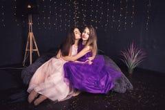 rozochocone dziewczyny Dwa długowłosej dziewczyny w menchii i purpur sukniach w studiu na ciemnym tle z bokeh kosmos kopii Obrazy Stock