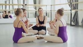Rozochocone dziewczyny i ich baletniczy nauczyciel biorą kawałki wyśmienicie pizza od pudełkowatego obsiadania na pracownianej po zbiory wideo