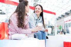 Rozochocone dziewczyny pije kawę w zakupy centrum handlowym obrazy royalty free