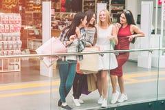 Rozochocone dziewczyny są przyglądającym each inny i ono uśmiecha się Stoją przy krawędzią szklana pokrywa Dziewczyny wydają zdjęcia stock