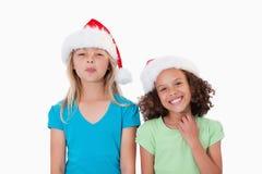 Rozochocone dziewczyny z Bożenarodzeniowymi kapeluszami Obraz Stock