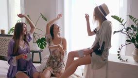 Rozochocone dziewczyny zabawę z filiżankami herbata i pudełko cukierki w domu w jedwabniczych nightwears przy lekkim pokojem zdjęcie wideo