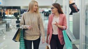 Rozochocone kobiety niesie papierowe torby są opowiadać i gestykulować podczas gdy chodzący wpólnie w shoppng centrum handlowym D zbiory wideo