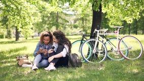 Rozochocone młode kobiety Kaukaskie i amerykanin afrykańskiego pochodzenia są opowiadający i używać smartphones w parku, dziewczy zbiory