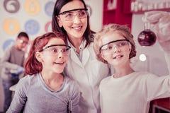 Rozochocone małe dziewczynki wymaga w chemicznym eksperymencie obrazy royalty free
