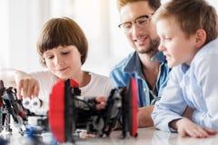 Rozochocone uśmiechnięte chłopiec pracuje na robotyka Obraz Royalty Free