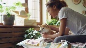 Rozochoconego amerykanina afrykańskiego pochodzenia nastolatka ładna dziewczyna siedzi na łóżku w domu snuggling ślicznego szczen zbiory