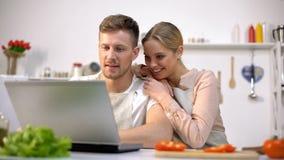 Rozochoconego pary dopatrywania kulinarni tutorials online, romantyczny obiadowy przygotowanie obrazy royalty free