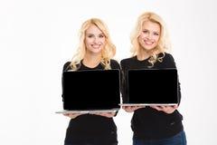 Rozochoconego wspaniałego blondynki siostrzanego bliźniaczego mienia laptopu pusty ekran Obrazy Royalty Free