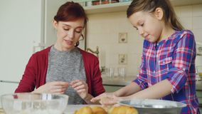 Rozochoconej matki i ślicznej córki toczny ciasto podczas gdy gotujący w kuchni na weekendzie Rodzina, jedzenie, dom i ludzie, zbiory wideo