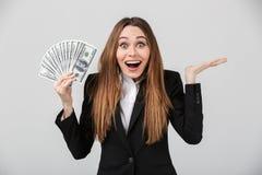 Rozochoconej zdziwionej damy przyglądająca kamera podczas gdy trzymający dolary w ręce obraz royalty free