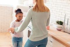 Rozochocony śmieszny matki i córki taniec w kuchni zdjęcie stock
