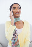 Rozochocony ładny kobiety obsiadanie na kanapie ma rozmowę telefonicza Obraz Stock