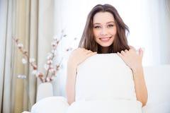 Rozochocony ładny młodej kobiety obsiadanie w łóżka i mienia poduszce Fotografia Royalty Free
