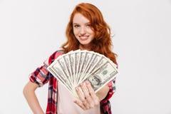 Rozochocony ładny młody rudzielec damy mienia pieniądze Fotografia Stock